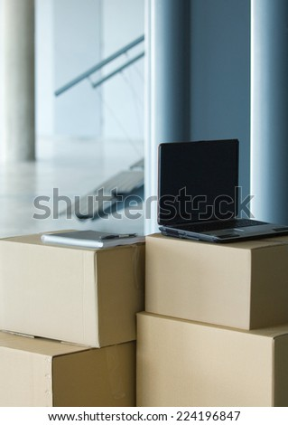 Laptop on top of stack of cardboard boxes - stock photo