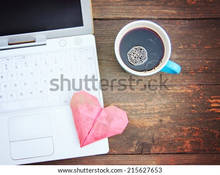 Laptop or notebook with cup of coffee and origami heart on old wooden table  - stock photo
