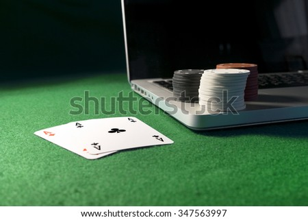 Laptop, poker cards and poker chips, on green background. - stock photo