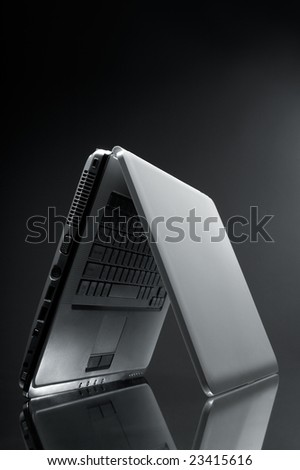 Laptop shot on reflective table on grey background - stock photo