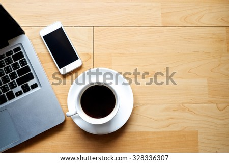 Laptop smart phone cup of coffee and notepad on wood background top view - stock photo