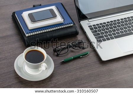 Laptop Smart Phone notebook and pen with a cup of coffee on the desk - stock photo