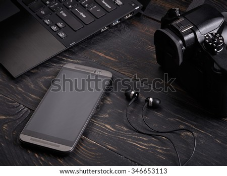 Laptop, smart phone, photo camera and headset on wooden background - stock photo