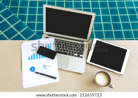 Laptop, tablet , smartphone and coffee cup with financial documents at swimming pool - stock photo