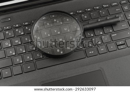 Laptop with a magnify glass - stock photo