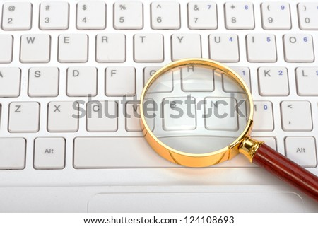Laptop with a magnifying glass - stock photo