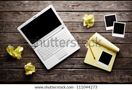 Laptop with blank instant photos and notepad with sheets of crumpled paper on old wooden table. Workplace writer. - stock photo