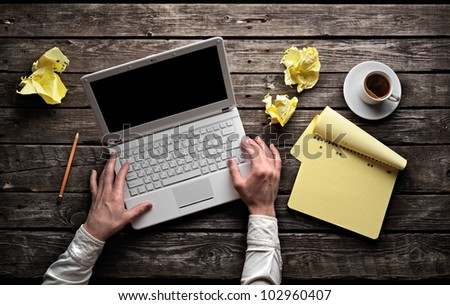 Laptop with blank notepad and pencil with sheets of crumpled paper on old wooden table. Workplace writer. - stock photo