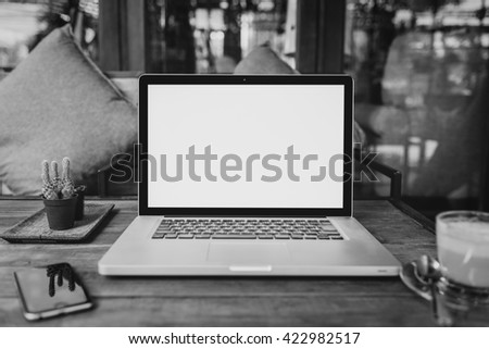 Laptop with blank screen on wood table. gray color laptop white screen - stock photo