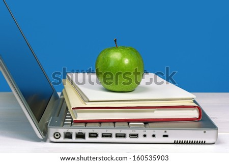 laptop with book, notebook and green apple - stock photo