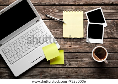 Laptop with coffee cup, instant photos and sticky note paper with notepad on old wooden table. - stock photo