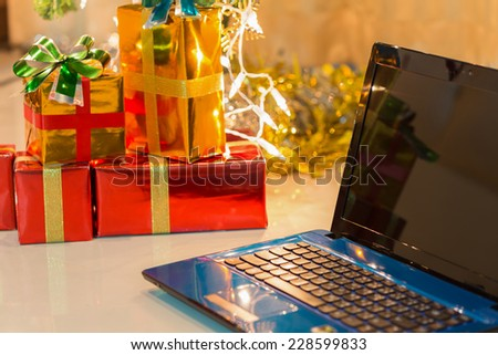laptop with gift box and christmas lights background - stock photo