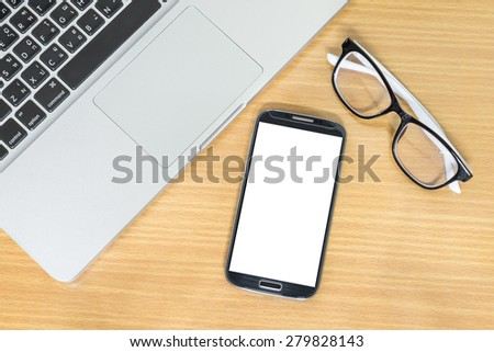 Laptop with glasses and smart phone on table - stock photo