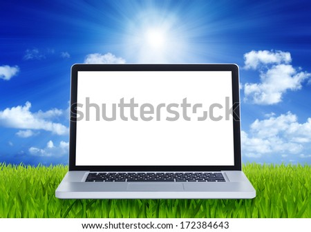 Laptop with green fields and blue sky background - stock photo