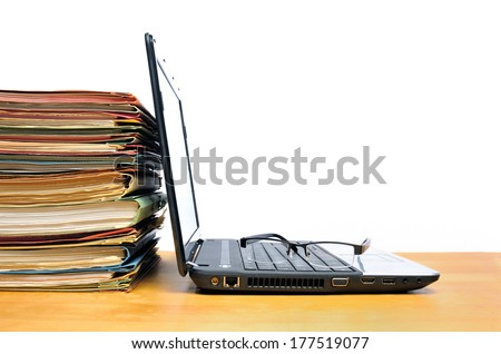 Laptop with multicolored office ring binders - stock photo