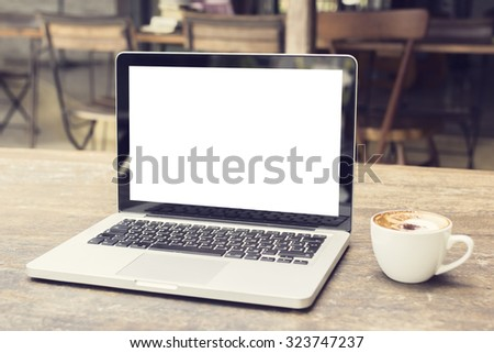 laptop with white screen on a table in a cafe, mock up - stock photo