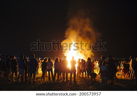 LAREDO, SPAIN - JUNE 24, 2014: People celebrate St John's Eve around a bonfire in a beach in northern Spain. St John's eve celebration around a bonfire is reminiscent of Midsummer's pagan rituals.  - stock photo