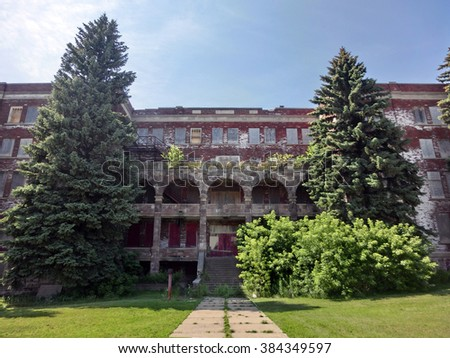 Large abandoned school exterior - landscape color photo - stock photo