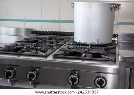 large aluminum pot over the stove's gas stainless steel industrial kitchen - stock photo