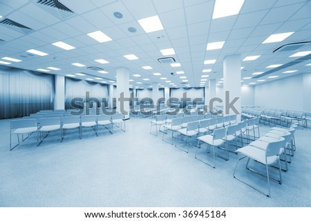 large and modern white auditorium with blue curtains - stock photo