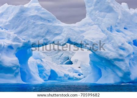 Large Antarctic iceberg with a cavity inside - stock photo
