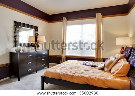 Large apartment bedroom with brightly lit window - stock photo