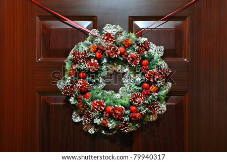 Large artificial circled wreath with knops and bead hangs during Christmas on door - stock photo