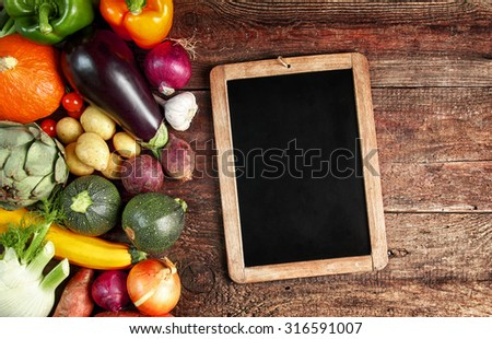 Large assortment of farm fresh whole uncooked autumn vegetables on a rustic wooden table alongside a vintage school slate with blank copyspace for a menu or recipe - stock photo