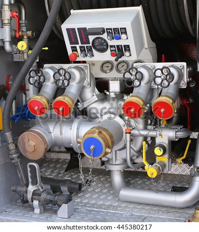 large automatic pump nozzles in fire truck with gauges and controls - stock photo