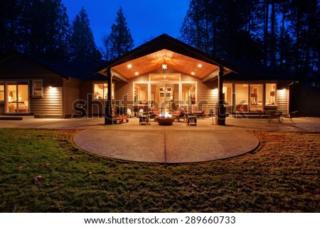 Large back yard with grass and covered patio with fire pit. - stock photo