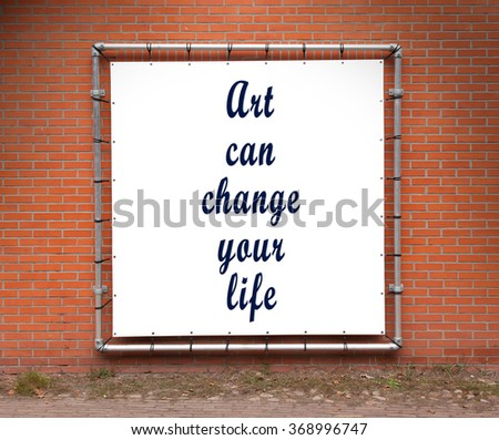 Large banner with inspirational quote on a brick wall - Art can change your life - stock photo
