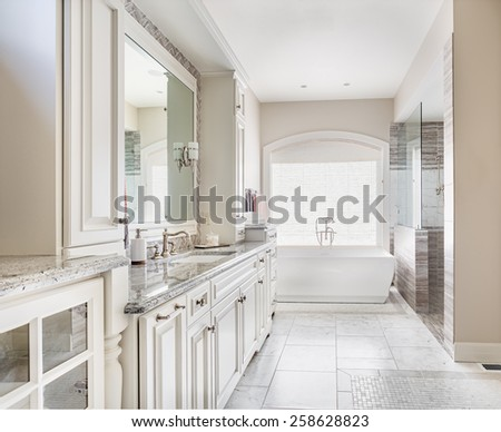 Large bathroom in luxury home with two sinks, tile floors, fancy cabinets, large mirrors, and bathtub - stock photo