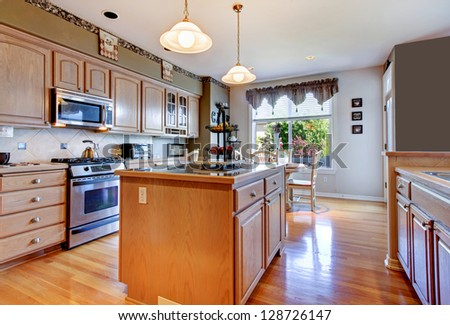 Large beautiful white kitchen with hardwood floor and green walls. - stock photo