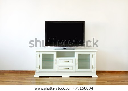 Large black widescreen TV set on the white dresser in a bright room - stock photo