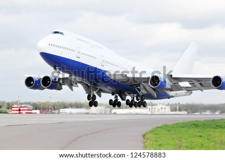 Large blue and white passenger airplane takes off at airport. - stock photo