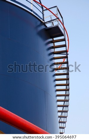 Large blue Industrial tank for petrol and oil with red ladder - stock photo