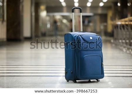 Large blue wheeled suitcase standing on the floor in modern airport terminal. Copy space - stock photo