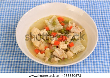 Large Bowl of chicken and dumplings soup  in clear broth with blue gingham place mat and blue background.  Setting is Southern or Country Style Cooking. - stock photo