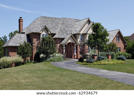 Large brick home with cedar shake roof - stock photo