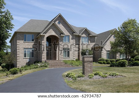 Large brick home with steps up to arched entry - stock photo