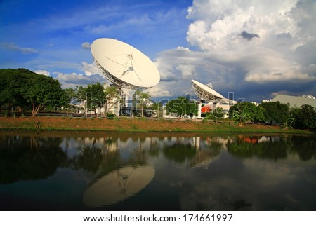 Large broadcast radars, satellite dishes, or radio telescopes with reflection on pond against blue sky - stock photo