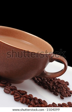 large brown coffee cup with blackbackground on white table with spilt coffee beans - stock photo