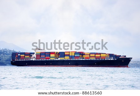 Large cargo ship in water carrying colorful shipping containers - stock photo
