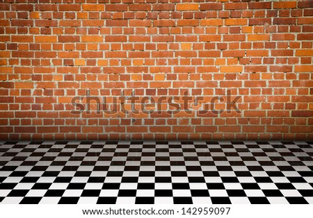 Large checker floor with brick wall - stock photo