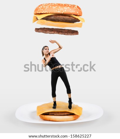 Large cheeseburger falling on a fit young woman - stock photo