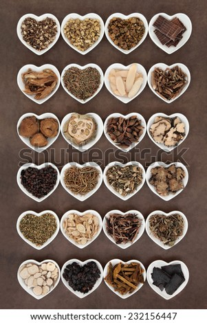 Large chinese herbal medicine selection in heart shaped porcelain bowls over lokta paper background. - stock photo