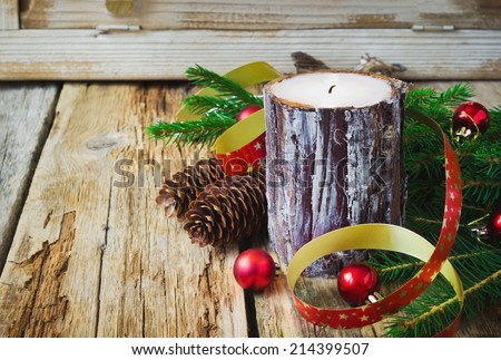 large christmas candle and christmas decorations on an old wooden table.holidays and events - stock photo