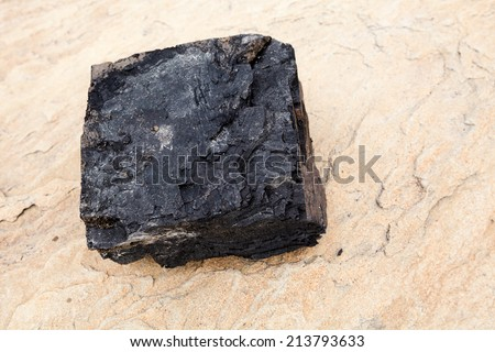 Large chunk of coal on beach. Dimensions around eight inches by eight inches by four inches. - stock photo
