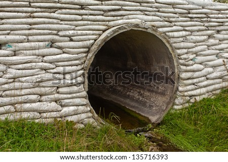 Large circular storm water culvert or drainage pipe infrastructure with concrete bank reinforcement - stock photo