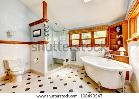 Large classic blue bathroom interior with tub and tiles and wood cabinets. - stock photo